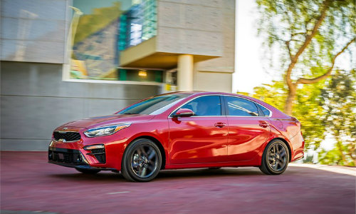 2019 Kia Forte exterior shot with red paint color parked outside a modern building near trees