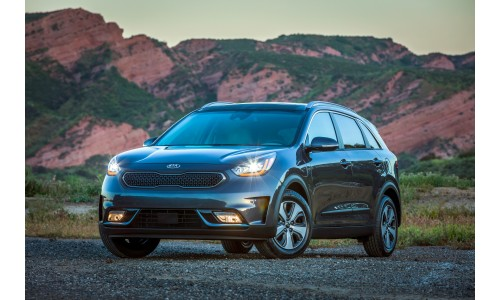 2019 Kia Niro Plug-In Hybrid exterior shot parked in the mountain wilderness with its headlights on