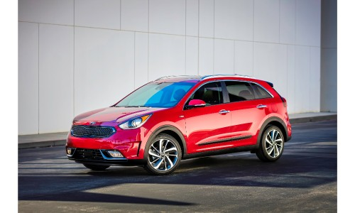 2019 Kia Niro exterior shot with red paint color parked alongside a white paneled wall