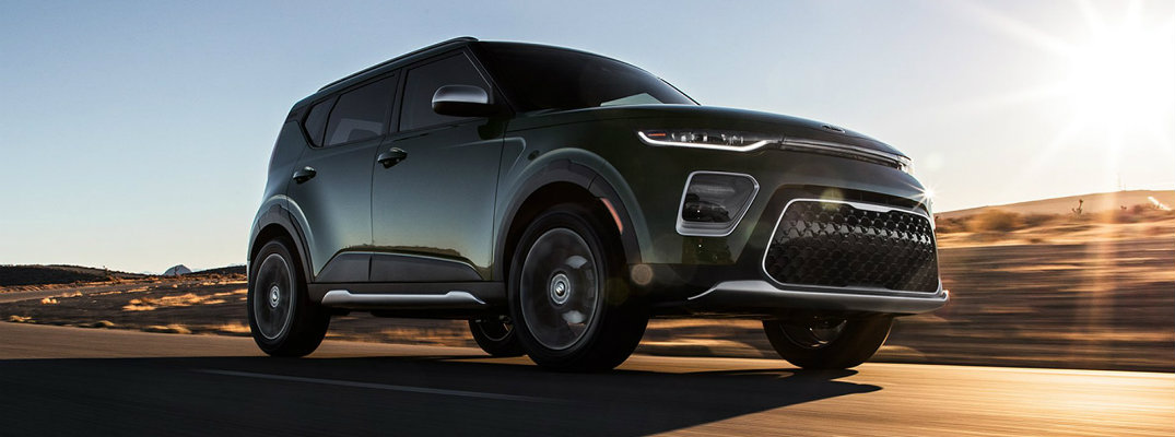 2020 Kia Soul exterior side shot with moss green paint color bathed in shadow under the sun as it drives down a desert highway