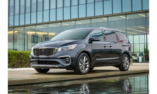 2019 Kia Sedona exterior shot with dark gray paint color parked outside a fancy car dealership near a pond