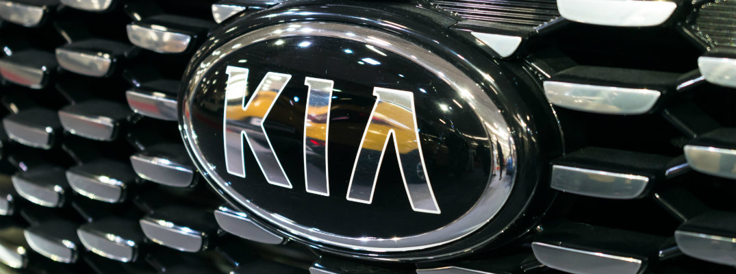 close up of a Kia badge on a Kia Sorento tiger nose grille shown at an auto show