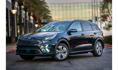2019 Kia Niro EV exterior shot parked outside a glass paneled dealership