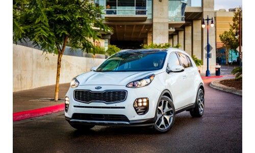 2019 Kia Sportage exterior front shot with white paint color parked outside a fancy California home