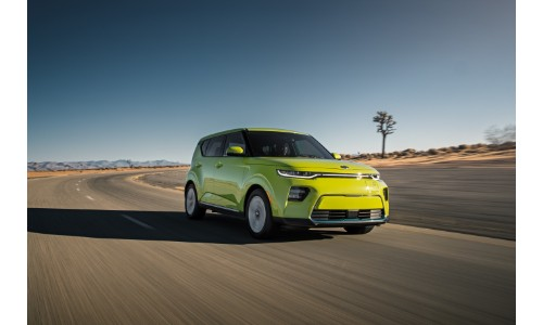 2020 Kia Soul EV exterior shot with lime green paint color driving down a desert highway