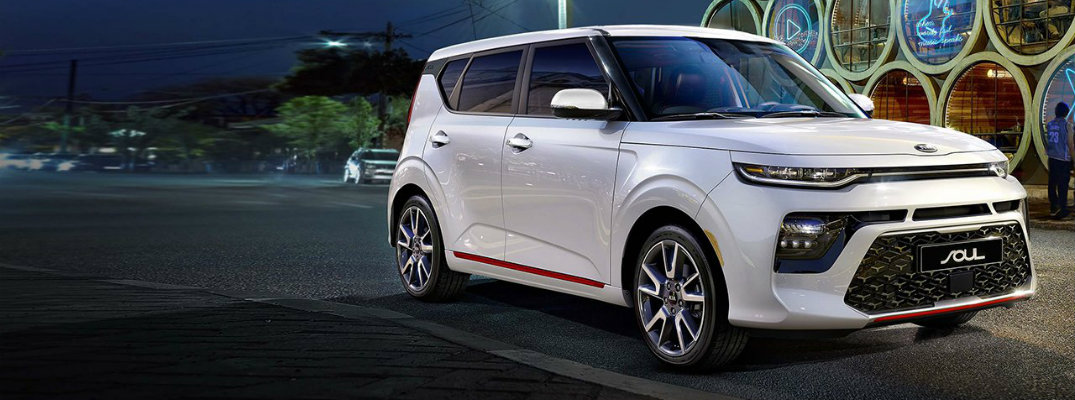 2020 Kia Soul exterior shot with white paint color and red trimming parked outside a fancy bar at night as a streetlight shines