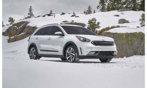 2019 Kia Niro exterior shot with white paint color parked in the snowy wilderness next to cliffs of rock