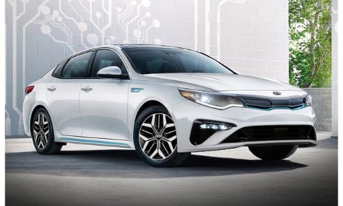 2020 Kia Optima Hybrid exterior shot with white paint color parked outside a white brick wall with code chip lines imprinted on the wall