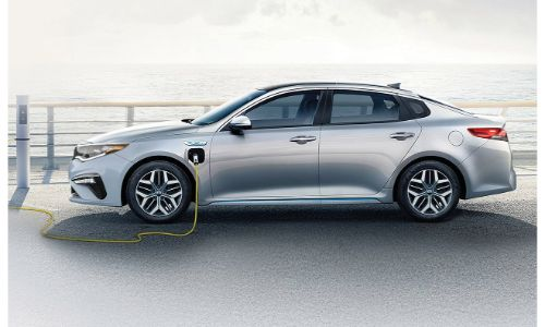 2020 Kia Optima PHEV Plug-In Hybrid exterior side shot with gray paint color plugged-in to a charging station near the sea