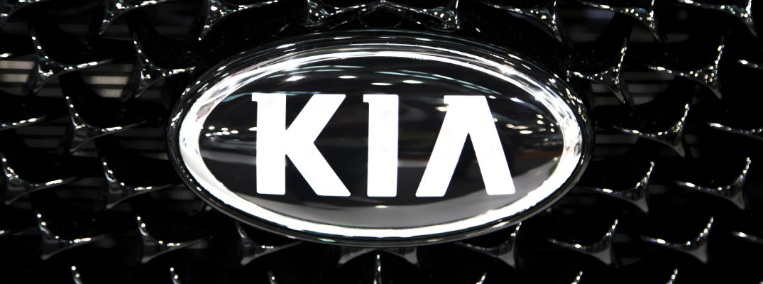 closeup shot of Kia logo badge on black mesh tiger nose grille