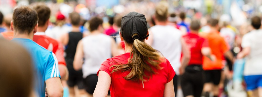 a close up on a woman runner surrounded by a crowd of other running marathon participants