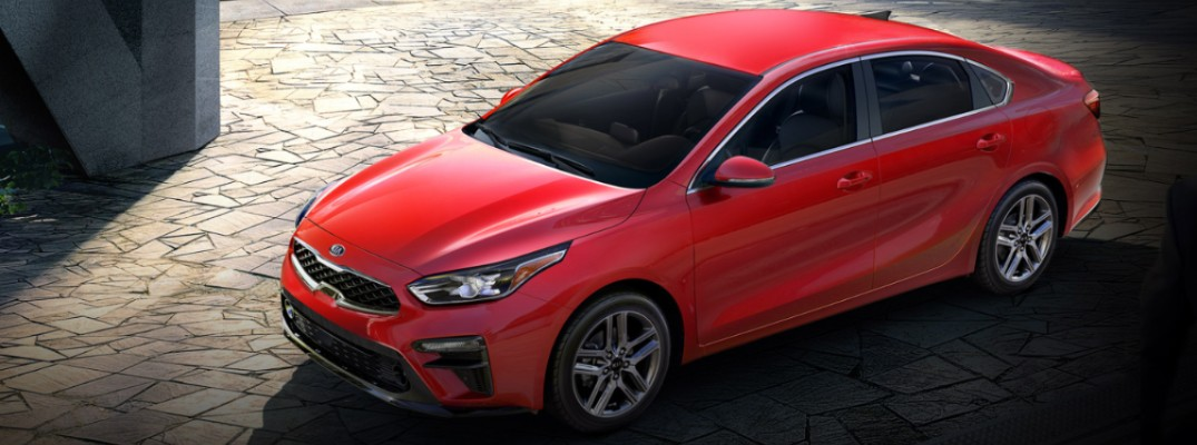 2020 Kia Forte exterior overhead shot on a stone tile plain lot with Currant Red paint color