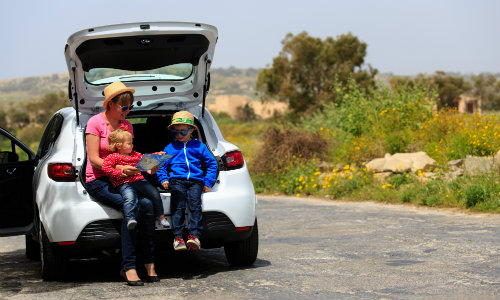 a family looking at a map while sitting on the bumper of an open car trunk while parked on the side of a country road