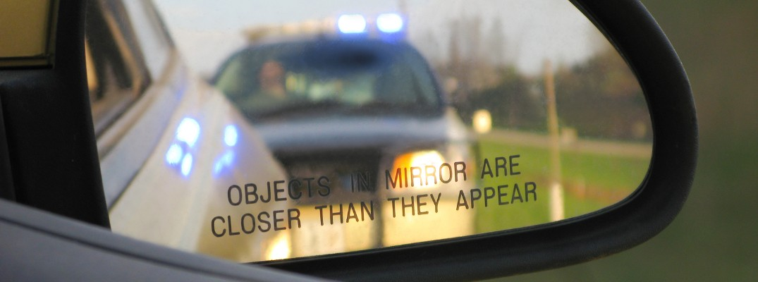 the view of a police car with its lights on from a side mirror of a driver caught in a traffic stop