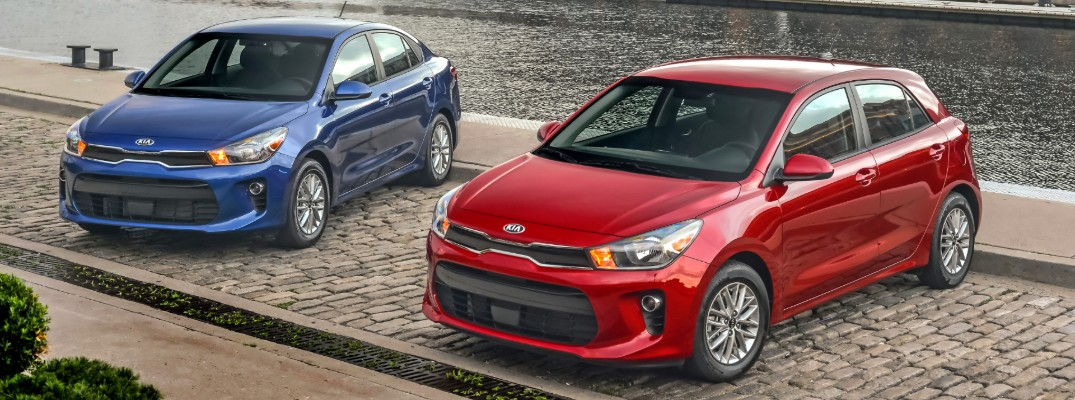 2020 Kia Rio sedan in blue and 2020 Kia Rio 5-door hatchback in red parked with a river canal