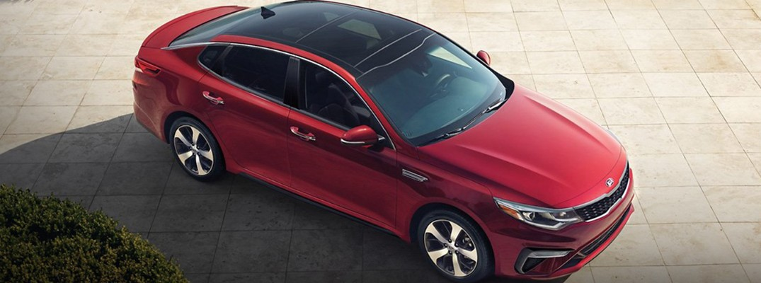2020 Kia Optima exterior overhead shot with passion red paint color parked on a stone tile plaza