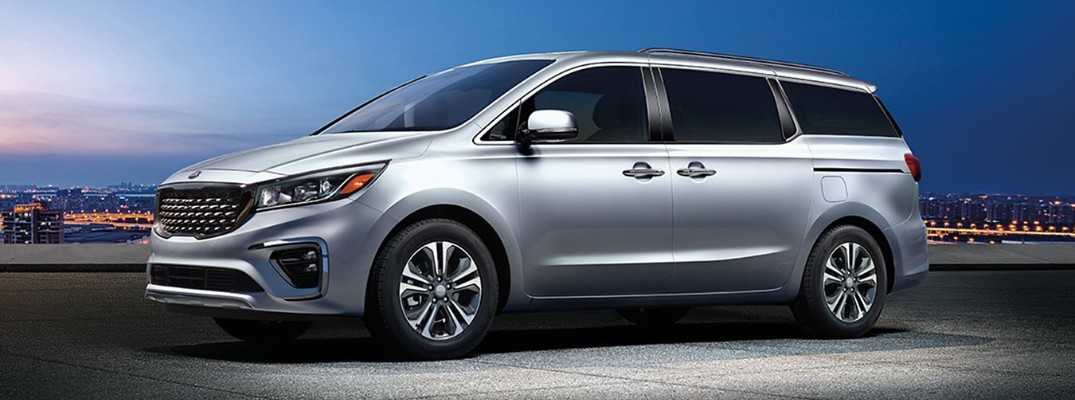 2020 Kia Sedona minivan exterior side shot with silky silver paint color parked on an empty lot under a light beam