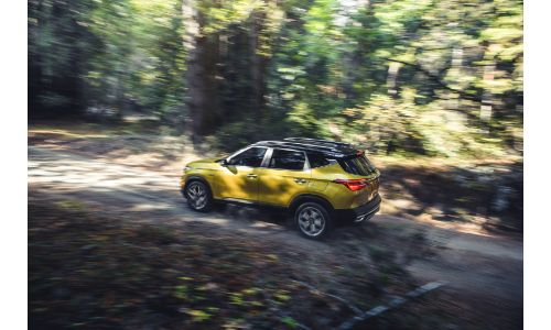2021 Kia Seltos exterior overhead side shot with gold paint color driving through a forest under the shadow of branches