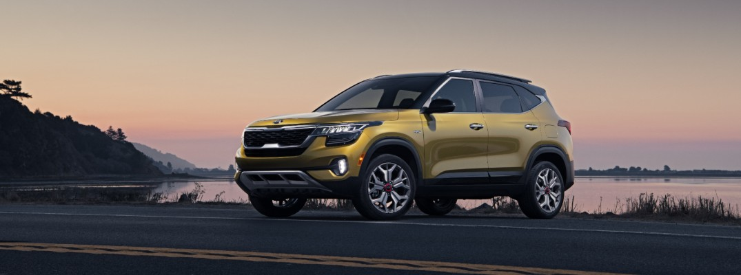 2021 Kia Seltos exterior side shot with gold paint color parked on the side of a highway near a lake as the sun sets and sky changes color