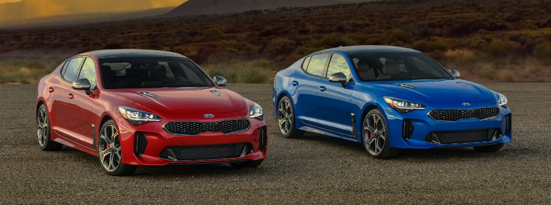 2020 Kia Stinger GT2 models exterior shot on gravel landscape in HiChroma Red and Micro Blue Pearl paint color options