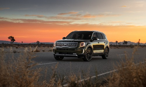 2020 Kia Telluride exterior shot with dark green paint color parked on a country highway as the sun sets