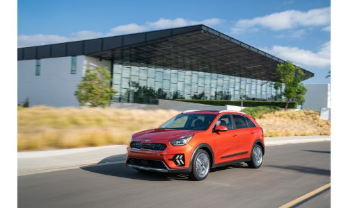 2020 Kia Niro Touring exterior shot with red paint color driving by a glass building near yellow grass
