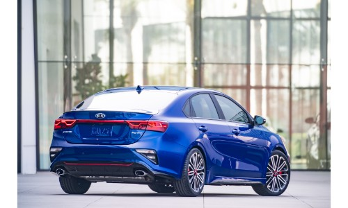 2020 Kia Forte GT exterior rear shot with blue paint color parked outside the glass walls of a car dealership