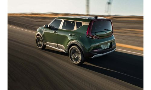 2020 Kia Soul X-Line exterior rear side shot with Undercover Green paint color driving on a desert highway