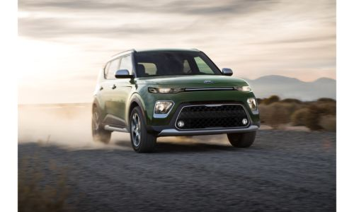 2020 Kia Soul X-Line exterior shot with Undercover Green paint color driving on a dirt road as dust and dirt are kicked up