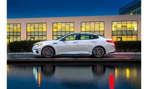 2020 Kia Optima exterior side shot with white paint color parked outside a dealreship at night