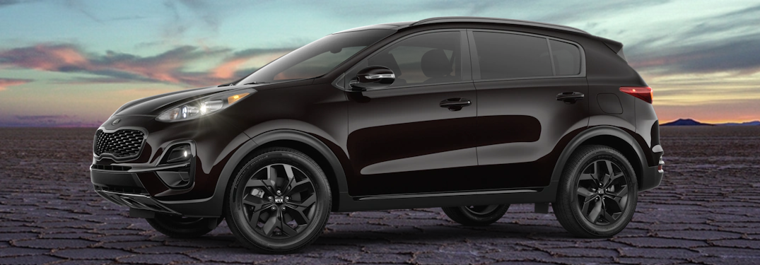 2021 Kia Sportage Nightfall Edition with Black Cherry paint color option exterior shot parked on dry and cracked desert earth