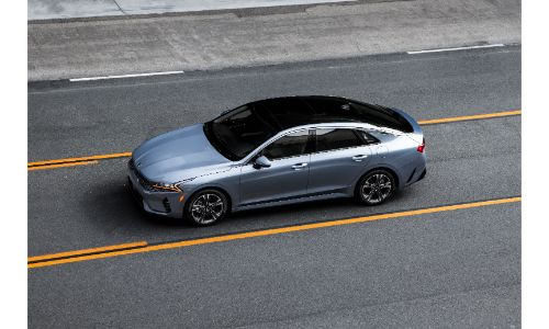 2021 Kia K5 GT-Line with Everlasting Silver paint color exterior overhead shot driving on a highway