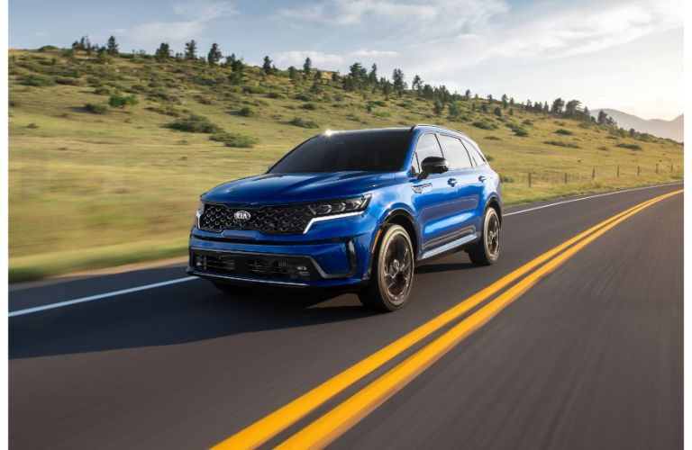 2021 Kia Sorento exterior shot with blue paint color driving down a country highway near hills of trees