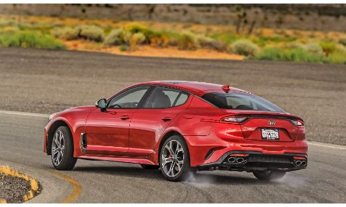 2021 Kia Stinger GT2 RWD exterior rear shot with red paint color driving on a country highway