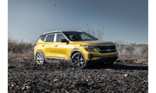 2021 Kia Seltos exterior shot with yellow paint color parked on an empty path of dirt and rocks