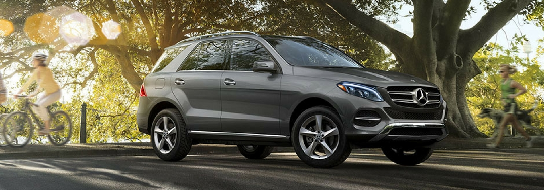 2018 Mercedes-Benz GLE driving through a park passing people running a biking