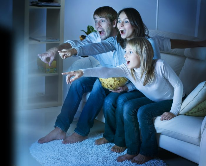 Family watching TV dramatically pointing at the screen