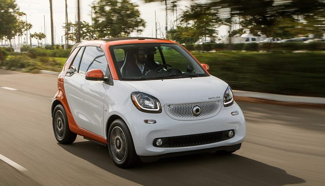 man driving a 2018 smart fortwo electric drive coupe on a road by a pier