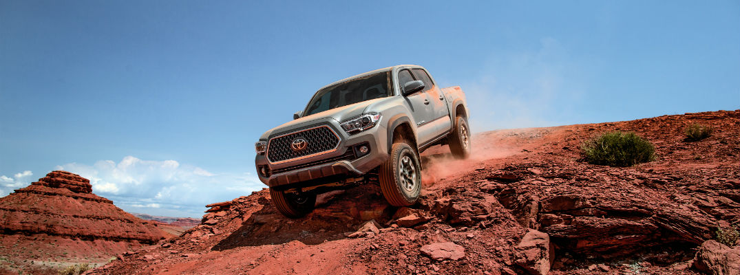 A photo of a 2018 Toyota Tacoma cresting a hill in the desert