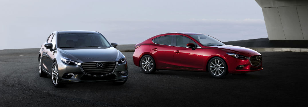 Front exterior view of a gray 2018 Mazda3 5-Door next to a passenger side exterior view of a red 2018 Mazda3 4-Door