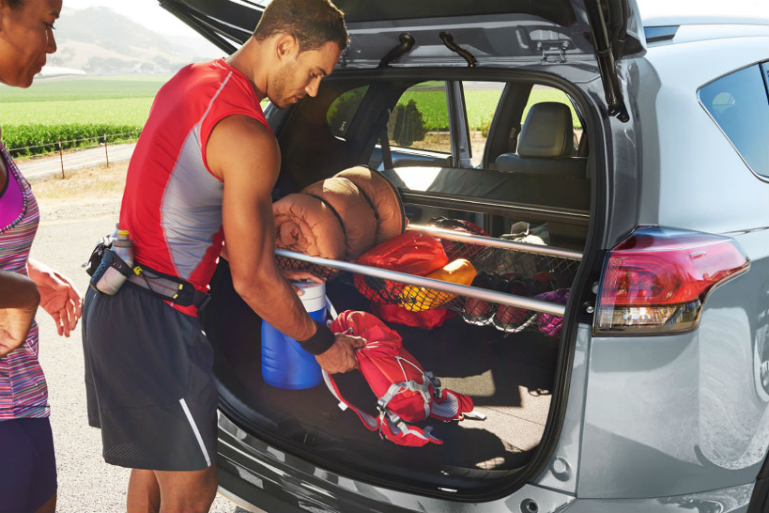 Man loading exercise equipment into the rear cargo area of the 2018 Toyota Rav4
