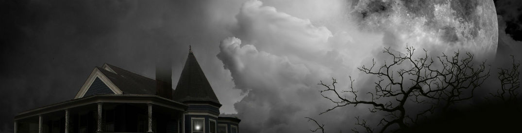 Heavy clouds covering a bright full moon above an old creepy haunted house