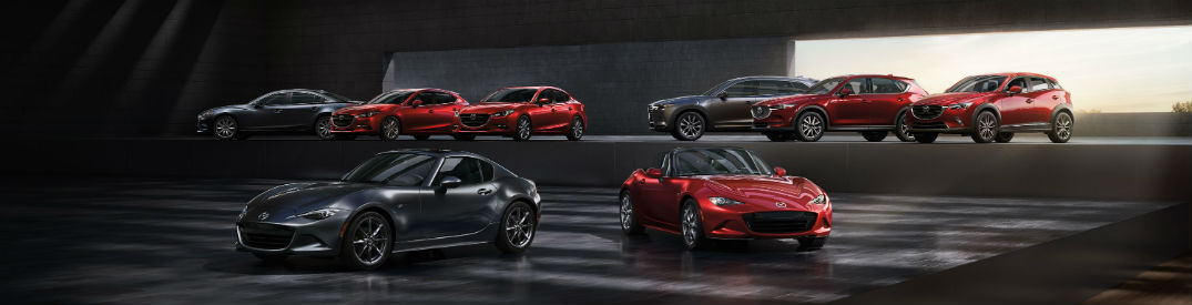 2018 Mazda vehicle lineup parked in a large room together with the MX-5 Miata front and center and all other models on a raised level in the background