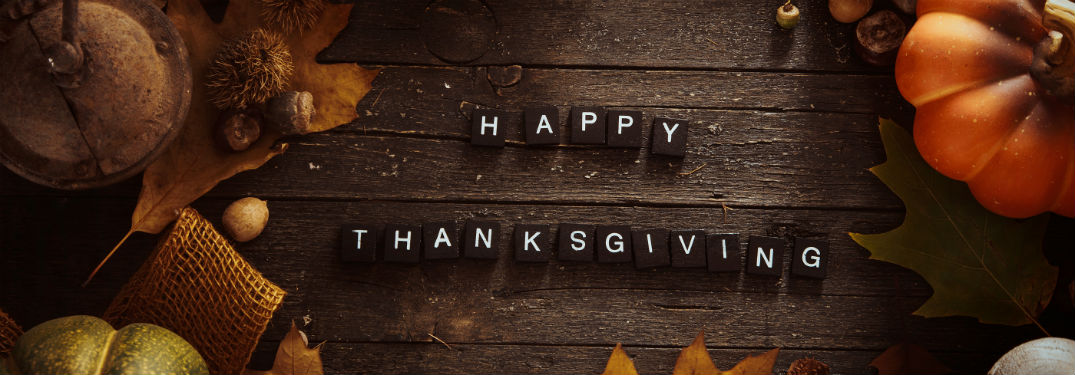 Happy Thanksgiving, text spelled out with lettered wood tiles on a wooden table surrounded by fall leaves