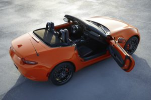 Overhead exterior view of an orange 2019 Mazda MX-5 Miata with the passenger door open