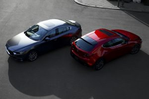 Overhead view of a black 2019 Mazda3 Sedan on the left parked next to a red 2019 Mazda3 Hatchback on the right