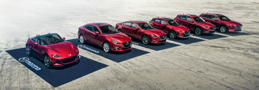 "The full 2019 Mazda vehicle lineup parked in the desert on black ""Mazda"" parking pads"