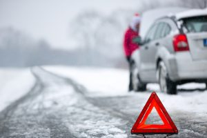warning triangle next to broken down car in winter