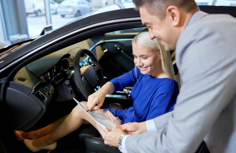 Car shopper in driver's seat with salesman explaining vehicle features