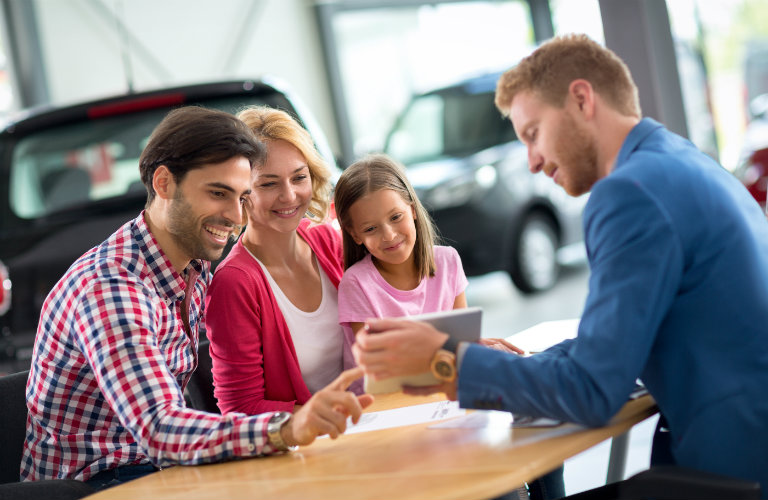 Couple talking with car salesman at desk